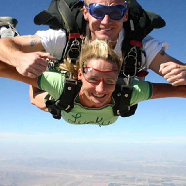 slika nasmejane ženske pri skoku s padalom