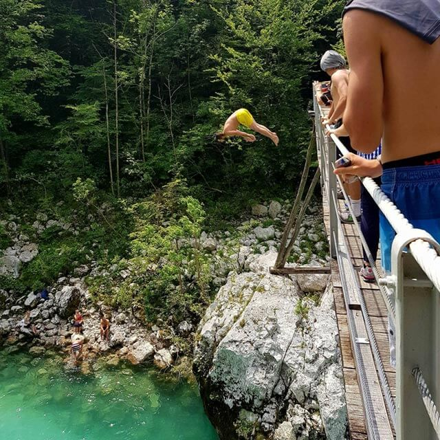 jumping from bridge into river with yelow bathing suit the river sava in slovenia
